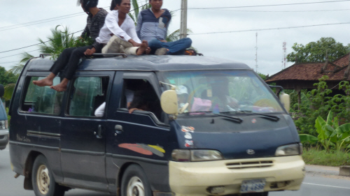 Passengers sitting Buddha-like on the mini-bus roof;