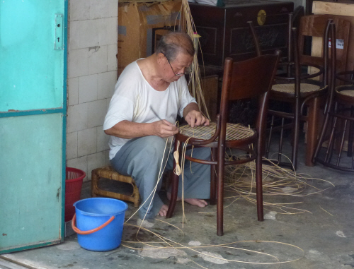 A craftsmen working away in one of Georgetown's shophouses.
