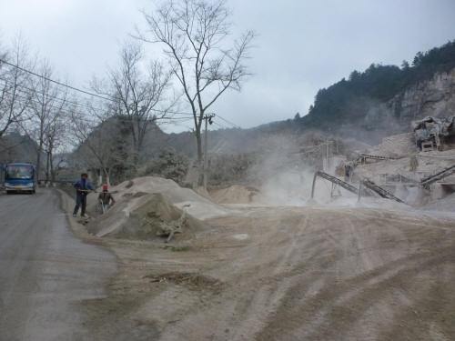A dust manufacturing quarry in full swing by the side of the road