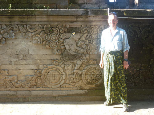 Keith, in the obligatory sarong, next to a carving at Meduwe Karang Temple depicting the Dutch artist W.O.J. Nieuwenkamp, who rode his bike around Bali in the early 1900s, painting as he went.